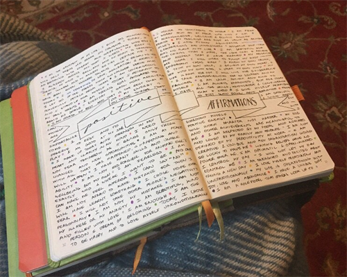 """An open journal full of notes with the words """"positive affirmations"""""""
