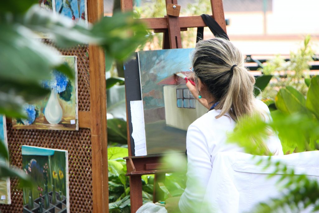 A person with long hair in a pony tail painting on a canvas with plants surrounding them
