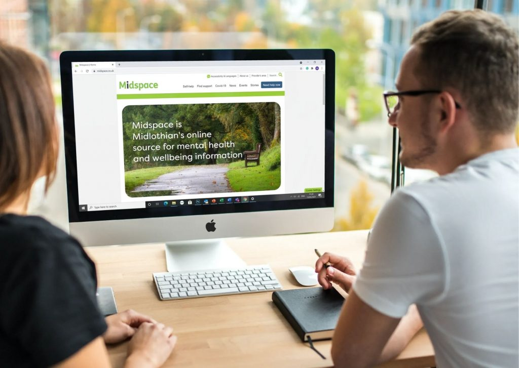 Two people looking at a computer screen with the Midspace website on the screen.