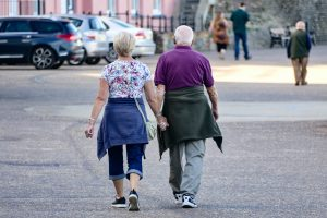 Two older people holding hands and walking through a car park. There are blurry figures in the background